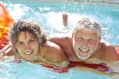 Couples mûrs détendant sur le matelas pneumatique dans la piscine Image stock