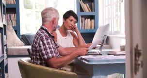 Couples mûrs dans le siège social regardant des écritures banque de vidéos