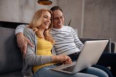 Couples mûrs de sourire utilisant l'ordinateur portable à la maison Photographie stock