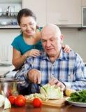 Couples mûrs faisant cuire la nourriture ensemble Photos stock