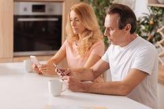 Couples mûrs hantés montrant la dépendance aux instruments à la maison Photos stock