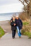 Couples mûrs heureux détendant des dunes de mer baltique image stock
