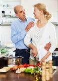 Couples mûrs heureux faisant cuire la nourriture avec des légumes Image stock