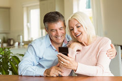 Couples mûrs heureux regardant le smartphone ensemble Photo stock