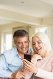 Couples mûrs heureux regardant le smartphone ensemble Image libre de droits