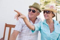Couples mûrs heureux se reposant sur le banc dans la ville Image stock