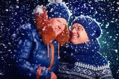 Couples mûrs heureux sous la neige Images stock