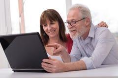 Couples mûrs heureux utilisant l'ordinateur portable Photos stock