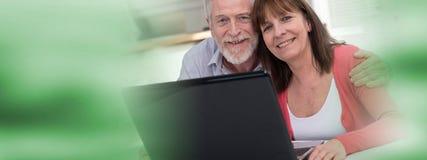 Couples mûrs heureux utilisant l'ordinateur portable Photos libres de droits