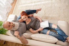 Couples mûrs heureux utilisant le comprimé numérique et sourire à l'appareil-photo photos stock
