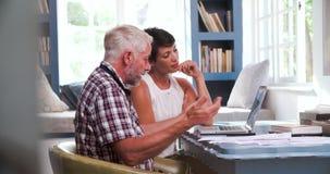 Couples mûrs inquiétés dans le siège social regardant des écritures banque de vidéos