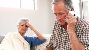 Couples mûrs inquiétés utilisant le smartphone sur le divan banque de vidéos