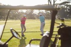 Couples mûrs jouant au golf photos stock