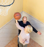 Couples mûrs jouant le basket-ball dans le patio Photo libre de droits