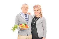 Couples mûrs jugeant un plat plein des légumes Image stock