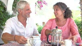 Couples mûrs mangeant le petit déjeuner dehors ensemble banque de vidéos
