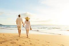 Couples mûrs marchant sur la plage au coucher du soleil images stock