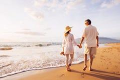 Couples mûrs marchant sur la plage au coucher du soleil photo stock