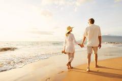 Couples mûrs marchant sur la plage au coucher du soleil image stock