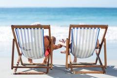 Couples mûrs mignons se trouvant sur des chaises longues Images stock