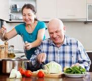 Couples mûrs ordinaires faisant cuire ensemble Image libre de droits