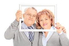 Couples mûrs posant derrière un cadre de tableau Photo stock