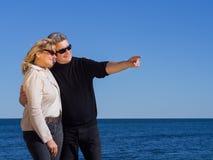Couples mûrs romantiques indiquant le copyspace à la côte Photo libre de droits