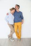 Couples mûrs se penchant sur l'embrassement de mur Photo stock