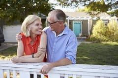 Couples mûrs se penchant sur la barrière d'arrière cour Photographie stock libre de droits