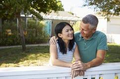 Couples mûrs se penchant sur la barrière d'arrière cour Images stock