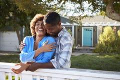 Couples mûrs se penchant sur la barrière d'arrière cour Photos stock