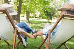 Couples mûrs se reposant dans des chaises de plate-forme au parc Photographie stock libre de droits