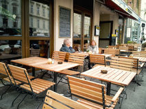 Couples mûrs se reposant dans un café vide de rue Photographie stock libre de droits