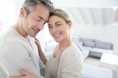 Couples mûrs sereins à la maison embrassant Image stock