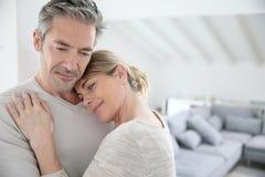 Couples mûrs sereins embrassant dans le salon Photo stock