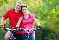Couples mûrs sur la bicyclette images libres de droits