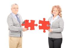 Couples mûrs tenant deux morceaux de puzzle Images libres de droits