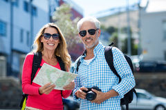Couples mûrs tenant la carte et l'appareil-photo dans la ville Photographie stock