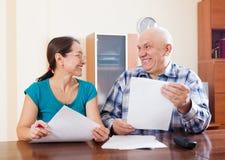 Couples mûrs tenant les documents financiers Image stock