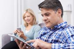 Couples mûrs utilisant des dispositifs de Digital à la maison images stock