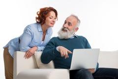 Couples mûrs utilisant l'ordinateur portatif Photographie stock libre de droits