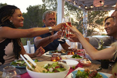 Couples make a toast at dinner on a roof terrace, close up Royalty Free Stock Images