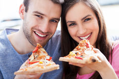 Couples mangeant de la pizza Photographie stock