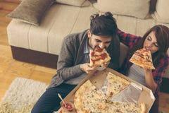 Couples mangeant de la pizza pour le déjeuner images libres de droits