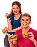 Couples mangeant des aliments de préparation rapide Hamburger de festin d'homme et de femme Photos stock