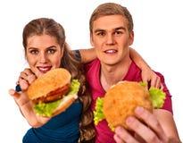 Couples mangeant des aliments de préparation rapide Hamburger de festin d'homme et de femme Images stock