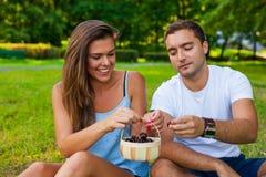 Couples mangeant des cerises de panier en parc Photo libre de droits