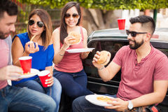 Couples mangeant des cheeseburgers à un barbecue Image libre de droits