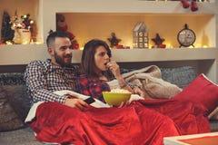 Couples mangeant des grains de bruit tout en regardant la TV Photographie stock