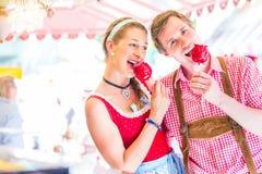 Couples mangeant des pommes de sucrerie chez Oktoberfest Photographie stock libre de droits
